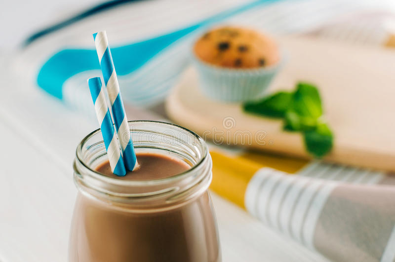 Ciérrese para arriba del chocolate caliente en la botella de cristal con el str rayado azul fotografía de archivo libre de regalías
