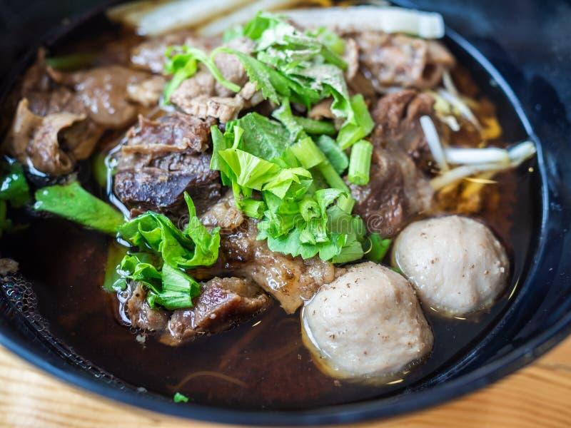 Ciérrese para arriba del cuenco negro de sopa de fideos de la carne de vaca del estilo chino foto de archivo libre de regalías