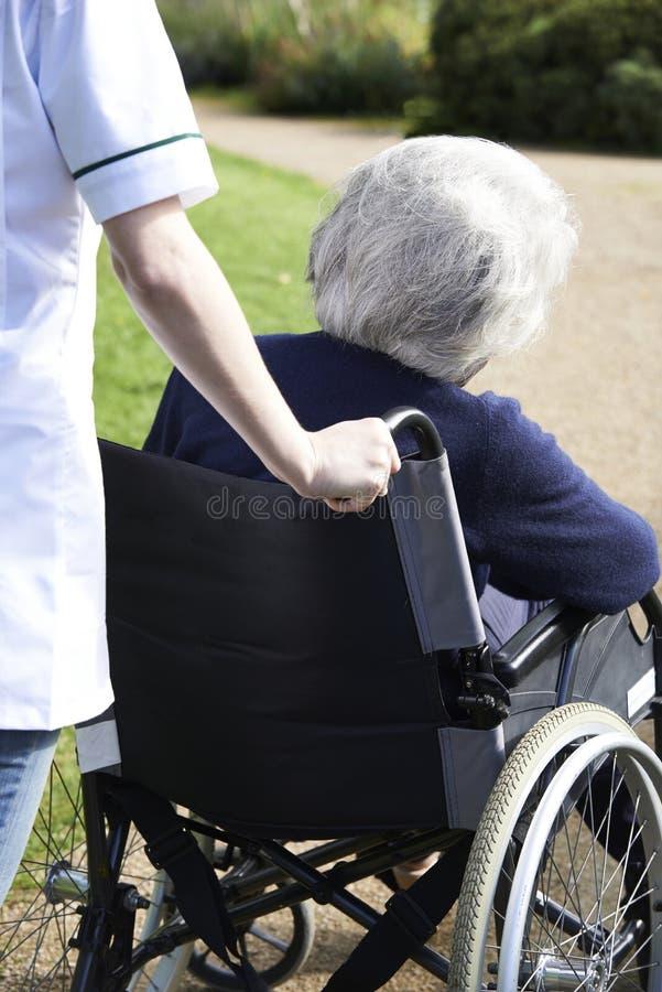 Ciérrese para arriba del cuidador que empuja a la mujer mayor en silla de ruedas foto de archivo libre de regalías