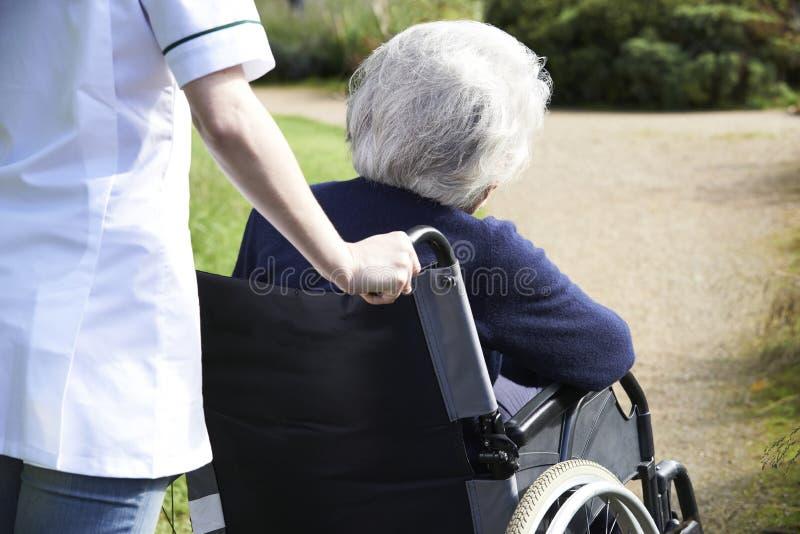 Ciérrese para arriba del cuidador que empuja a la mujer mayor en silla de ruedas imagenes de archivo