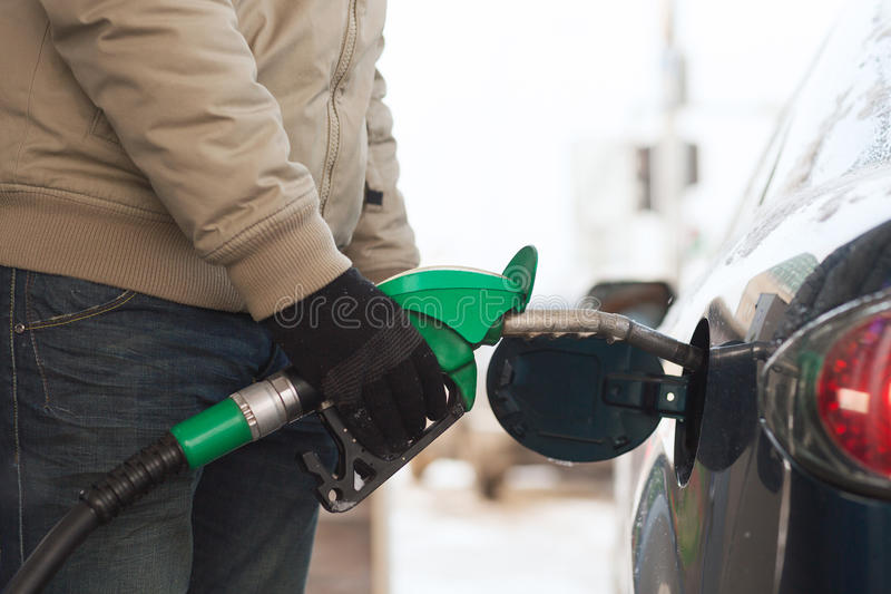 Ciérrese para arriba del depósito de gasolina masculino del coche que rellena imagen de archivo libre de regalías