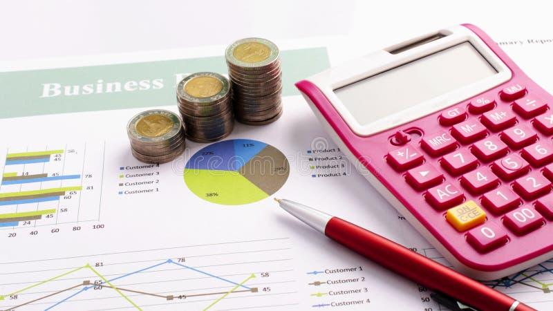 Ciérrese para arriba del dinero de la moneda y de la pluma rosada del calculadora y roja con el informe de negocios foto de archivo