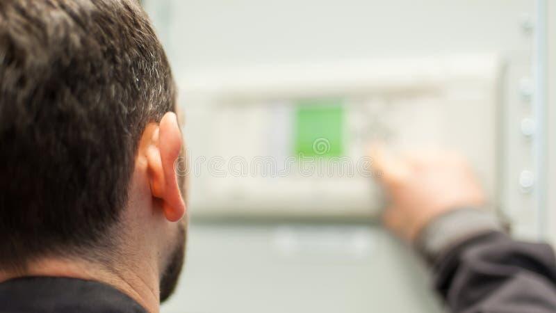 Ciérrese para arriba del dispositivo de distribución del voltaje de la prueba del ingeniero del mantenimiento imagen de archivo