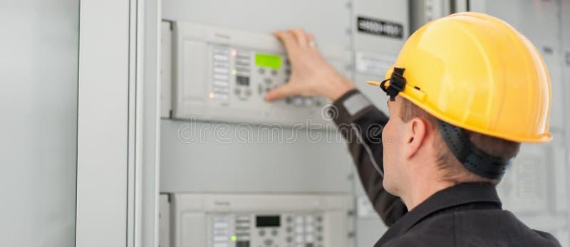 Ciérrese para arriba del dispositivo de distribución del voltaje de la prueba del ingeniero del mantenimiento fotografía de archivo