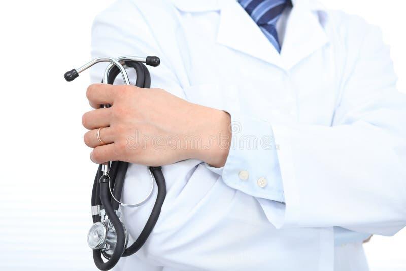 Ciérrese para arriba del doctor de sexo masculino desconocido que se coloca recto mientras que sostiene el estetoscopio Concepto  fotografía de archivo