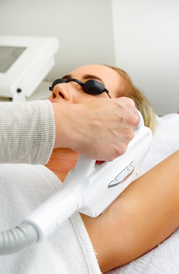 Ciérrese para arriba del doctor que usa un retiro del pelo del laser en un cliente del brazo de la mujer foto de archivo