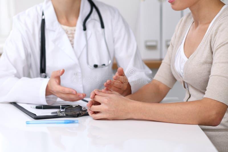 Ciérrese para arriba del doctor y del paciente que se sientan en el escritorio mientras que médico que señala en la forma médica  fotos de archivo