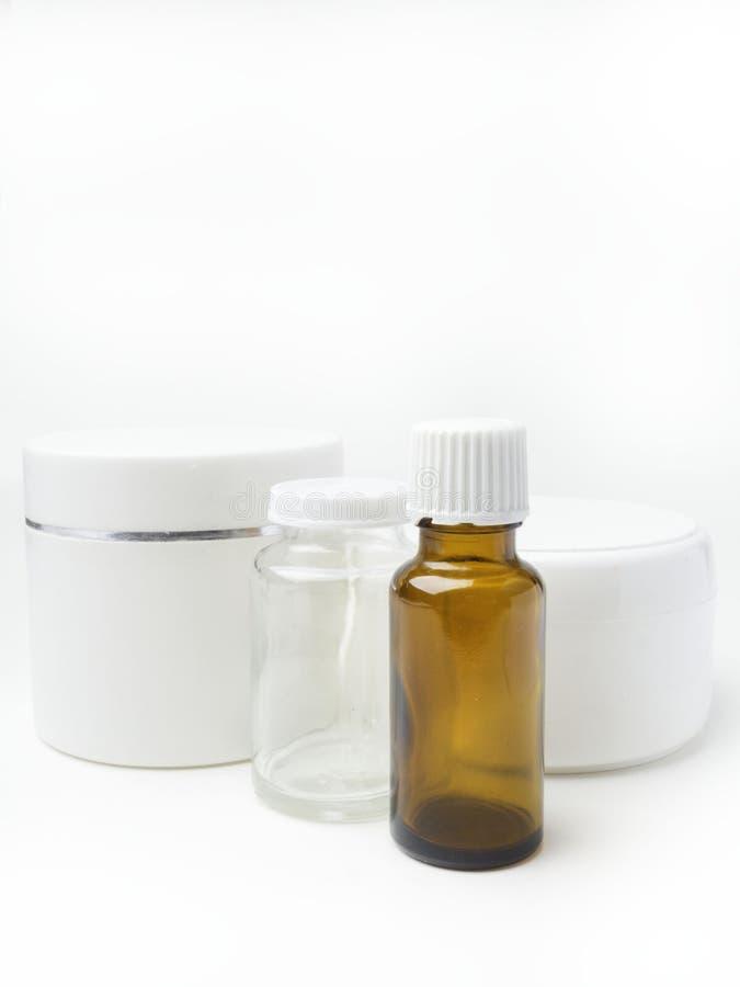 Ciérrese para arriba del envase de la higiene de la belleza en el fondo blanco con las botellas de vidrio del aceite esencial imagen de archivo