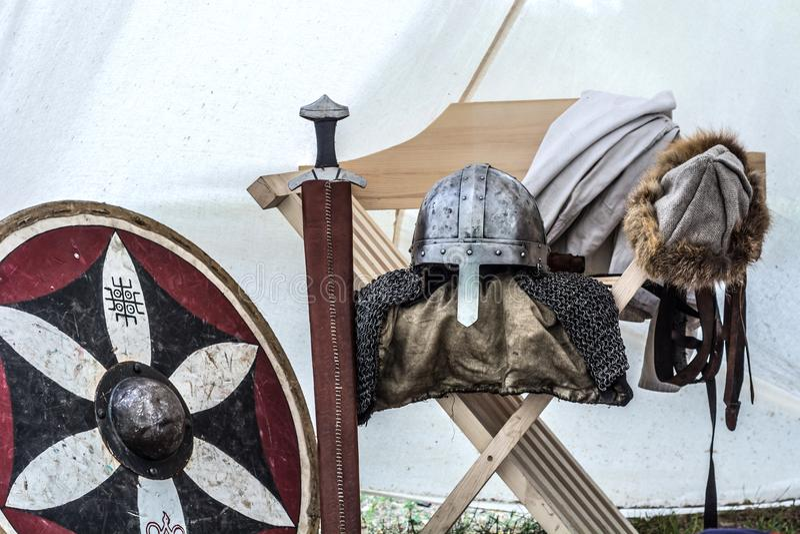 Ciérrese para arriba del equipo medieval del caballero en tienda vieja el dormir Casco del metal, escudo, espada imagen de archivo