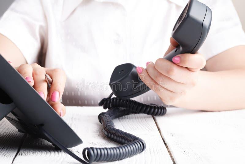 Ciérrese para arriba del finger que marca para hacer una llamada de teléfono en oficina fotos de archivo