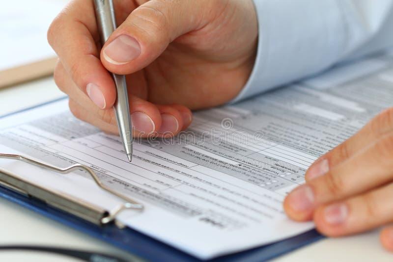 Ciérrese para arriba del formulario de impuesto de relleno del contable de sexo masculino imagen de archivo