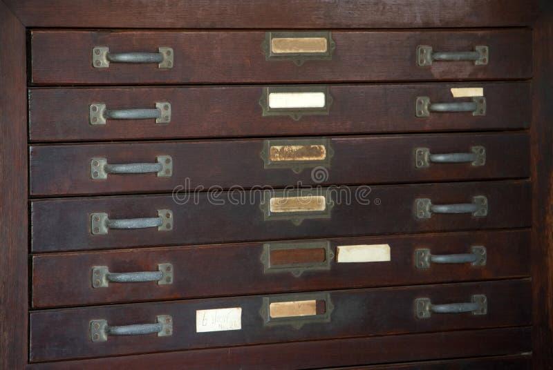 Ciérrese para arriba del gabinete de madera vertical del viejo vintage con el cajón, las manijas, las placas y la etiqueta resist fotografía de archivo