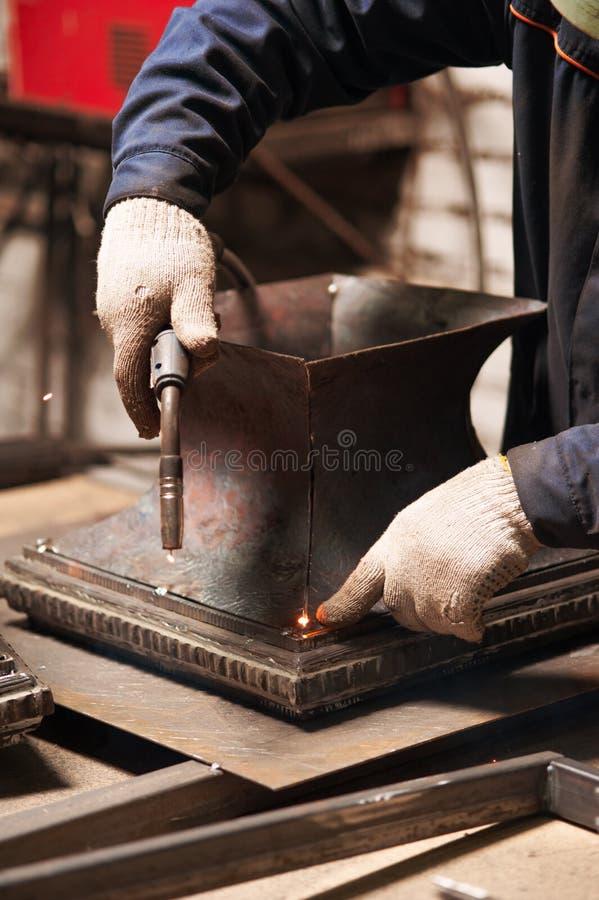 Ciérrese para arriba del herrero que suelda una placa de metal imagenes de archivo