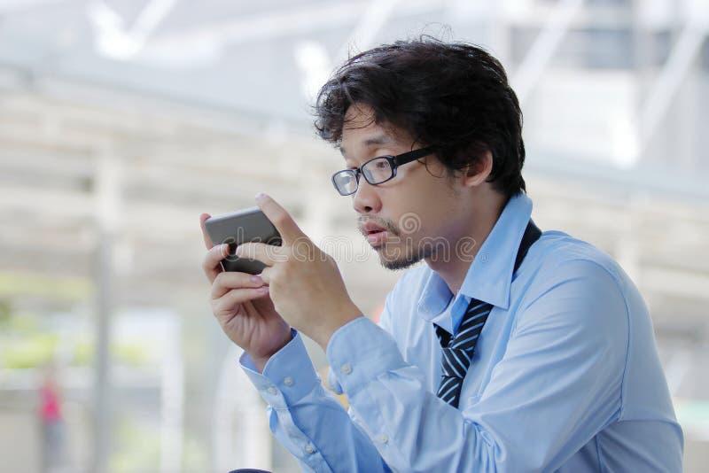 Ciérrese para arriba del hombre asiático joven parado que mira el teléfono elegante móvil para el trabajo del hallazgo Concepto d fotos de archivo