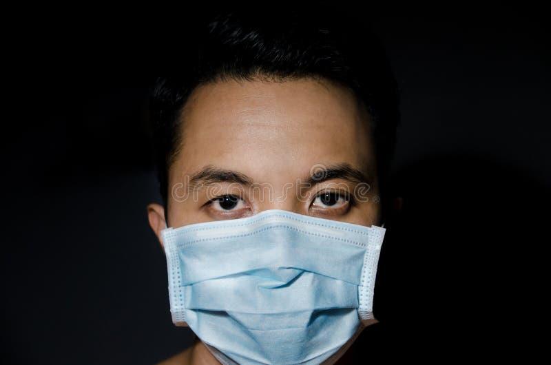 Ciérrese para arriba del hombre asiático joven que lleva la máscara higiénica fotografía de archivo libre de regalías