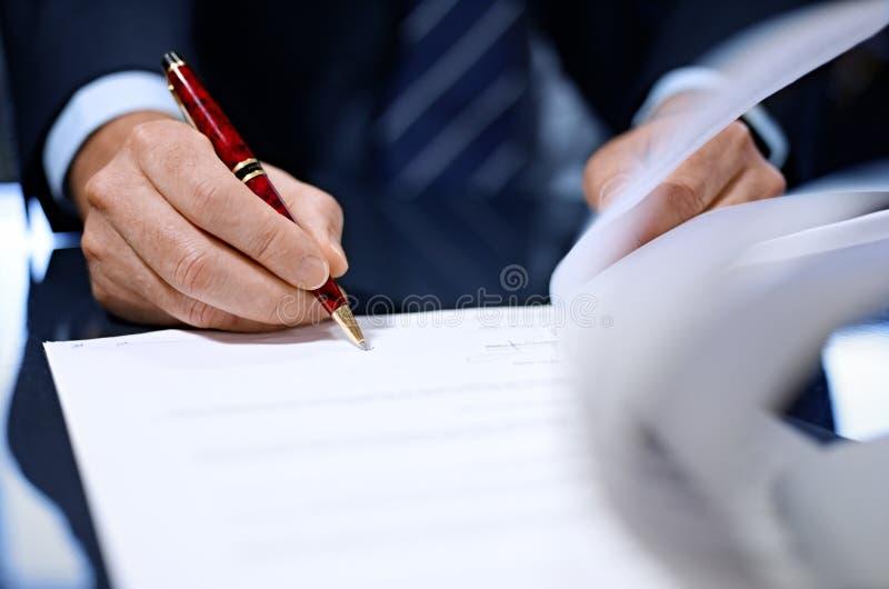 Ciérrese para arriba del hombre de negocios que firma un contrato. imagenes de archivo
