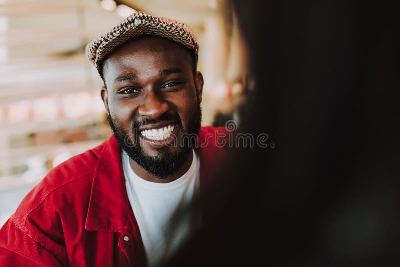 Ciérrese para arriba del hombre joven expresivo que revela sus dientes mientras que sonríe imagenes de archivo