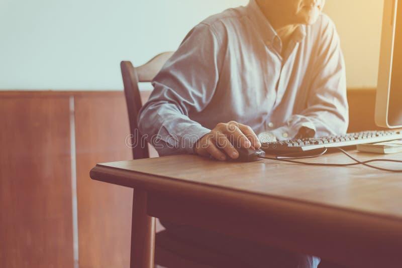 Ciérrese para arriba del hombre mayor de las manos que hace clic el ratón y que usa el ordenador en la tabla fotos de archivo