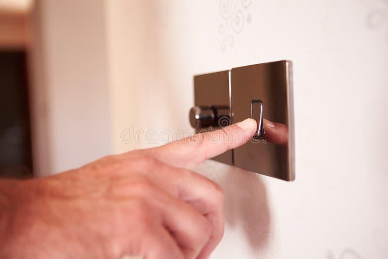 Ciérrese para arriba del hombre que gira el interruptor de la luz eléctrico imágenes de archivo libres de regalías