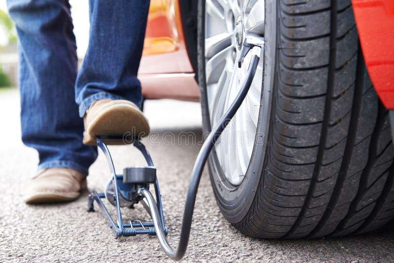 Ciérrese para arriba del hombre que infla el neumático del coche con la bomba de pie imagen de archivo
