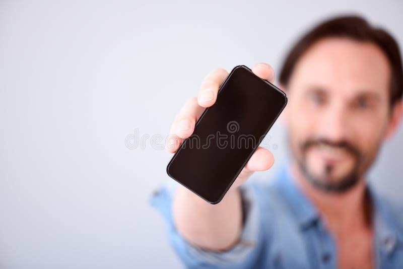 Ciérrese para arriba del hombre que muestra el teléfono elegante imagen de archivo