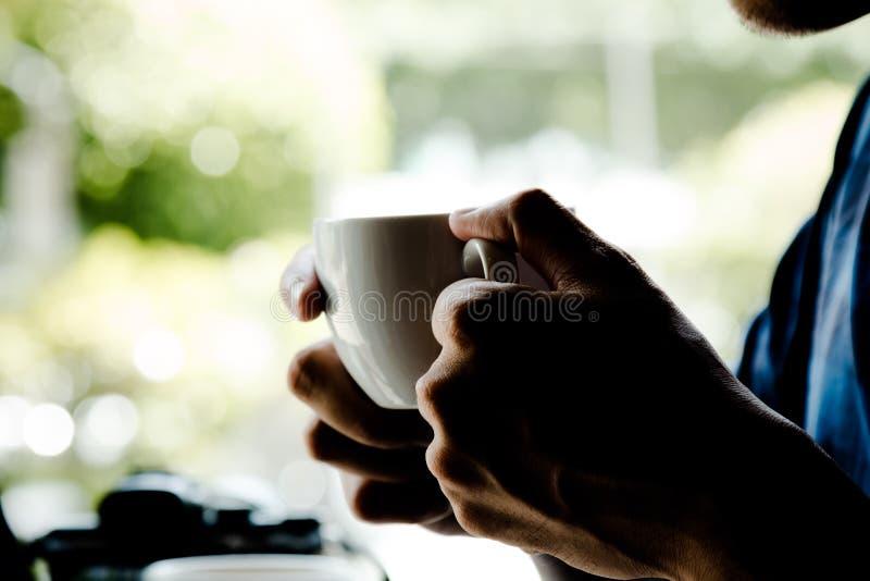 Ciérrese para arriba del hombre que sostiene la taza de café caliente del latte por tiempo de la rotura fotos de archivo libres de regalías
