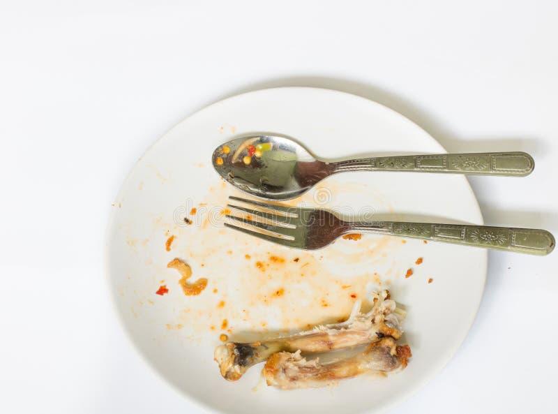 Ciérrese para arriba del hueso del pollo en el plato blanco con con la comida inútil foto de archivo libre de regalías