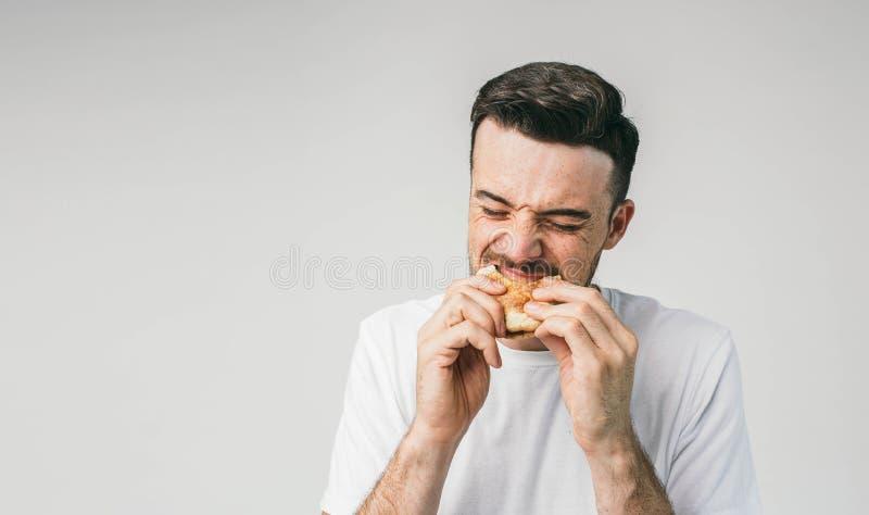 Ciérrese para arriba del individuo hermoso que muerde una hamburguesa Él lo está mordiendo muy difícilmente El hombre joven esper fotografía de archivo libre de regalías
