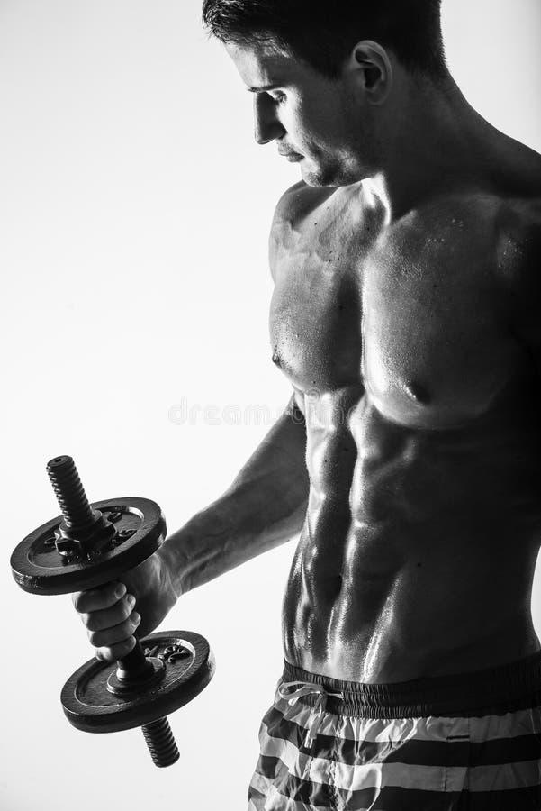 Ciérrese para arriba del individuo muscular del culturista que hace ejercicios con pesa de gimnasia de los pesos sobre fondo lige foto de archivo libre de regalías
