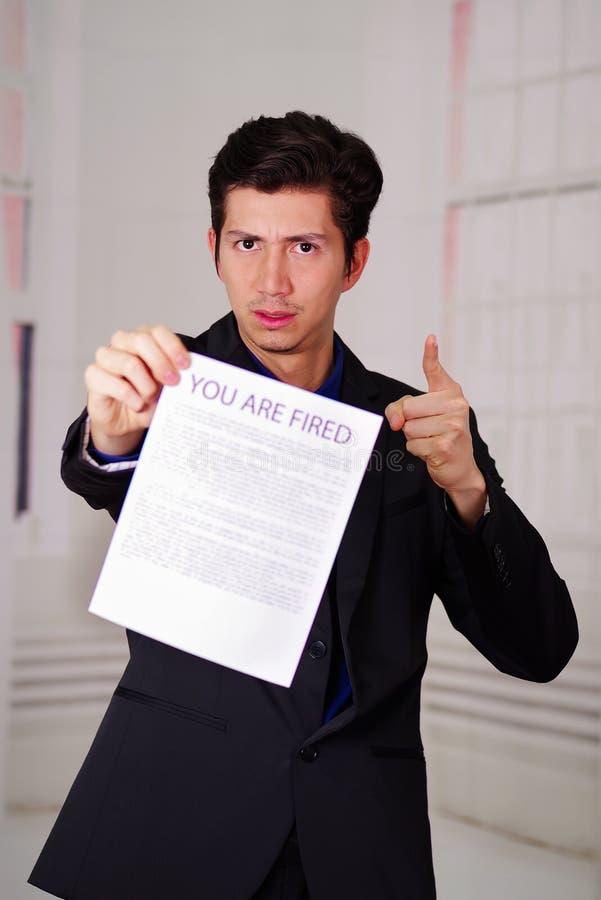 Ciérrese para arriba del jefe que lleva un traje y que sostiene una hoja de papel de usted ` con referencia al texto encendido en imagenes de archivo