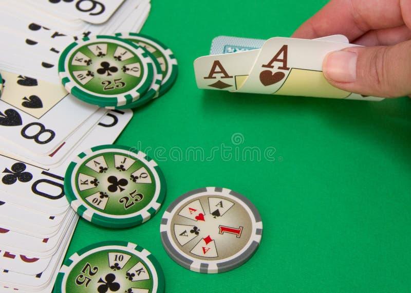 Ciérrese para arriba del jugador de póker que levanta las esquinas de dos tarjetas imagenes de archivo