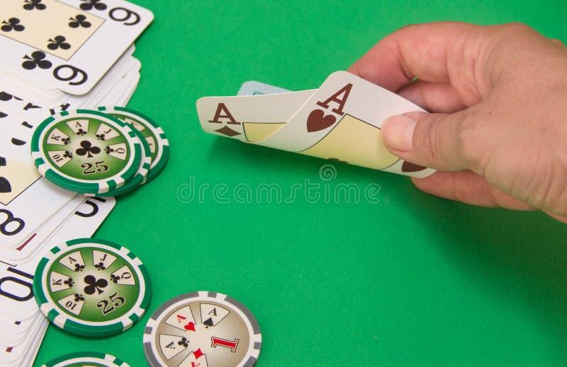 Ciérrese para arriba del jugador de póker que levanta las esquinas de dos tarjetas imagen de archivo