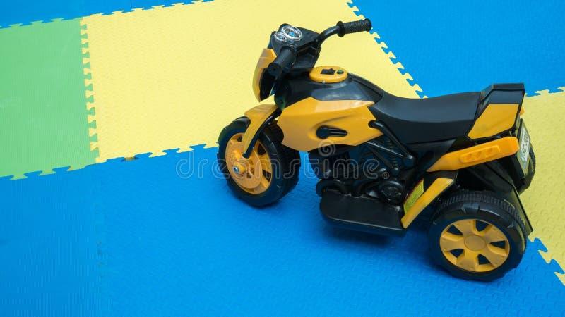Ciérrese para arriba del juguete amarillo de la motocicleta en el piso de goma con el espacio de la copia en el patio fotografía de archivo