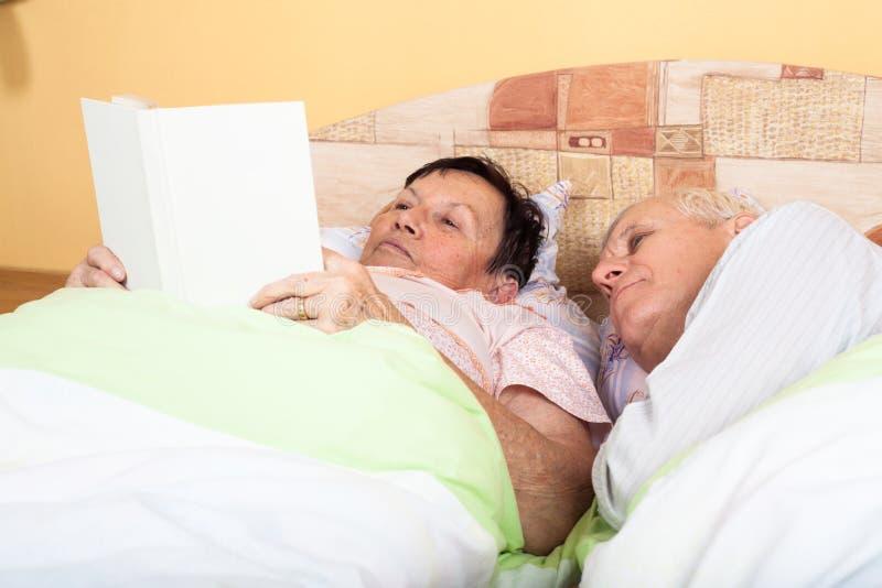 Libro de lectura mayor de los pares en cama imagenes de archivo
