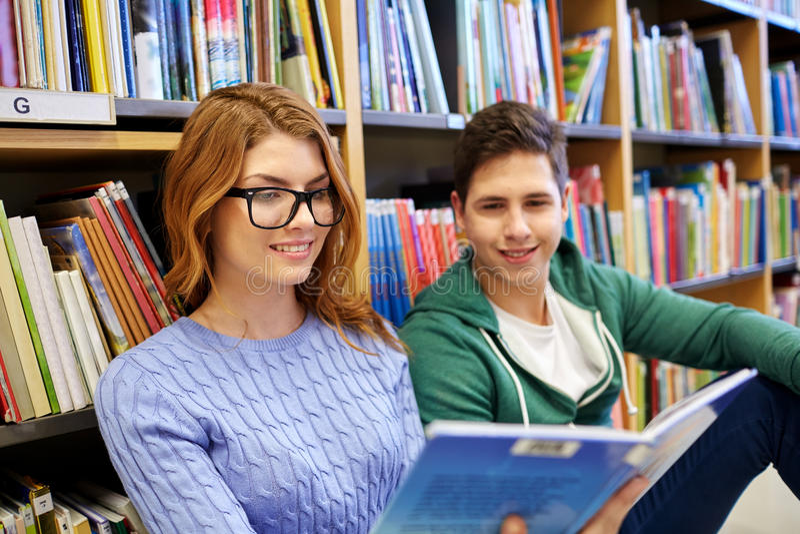 Ciérrese para arriba del libro de lectura feliz de los estudiantes en biblioteca fotos de archivo
