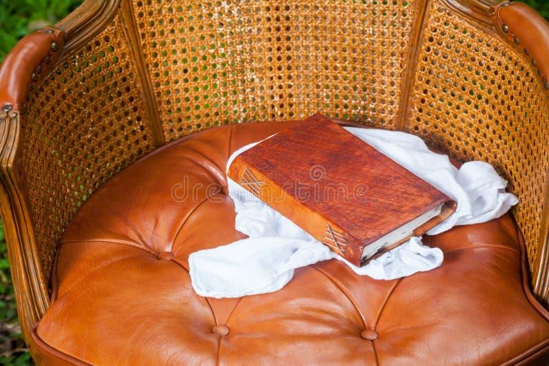 Ciérrese para arriba del libro viejo con cuero en la silla imagen de archivo