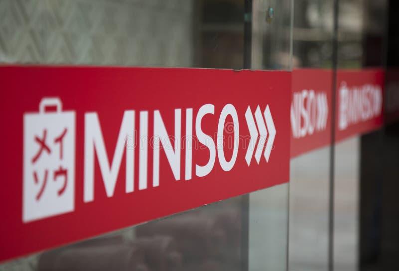 Ciérrese para arriba del logotipo de Miniso delante de una tienda fotografía de archivo libre de regalías