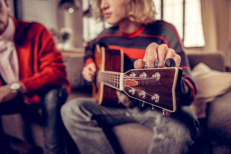Ciérrese para arriba del músico rubio-cabelludo que toca la guitarra en casa fotos de archivo