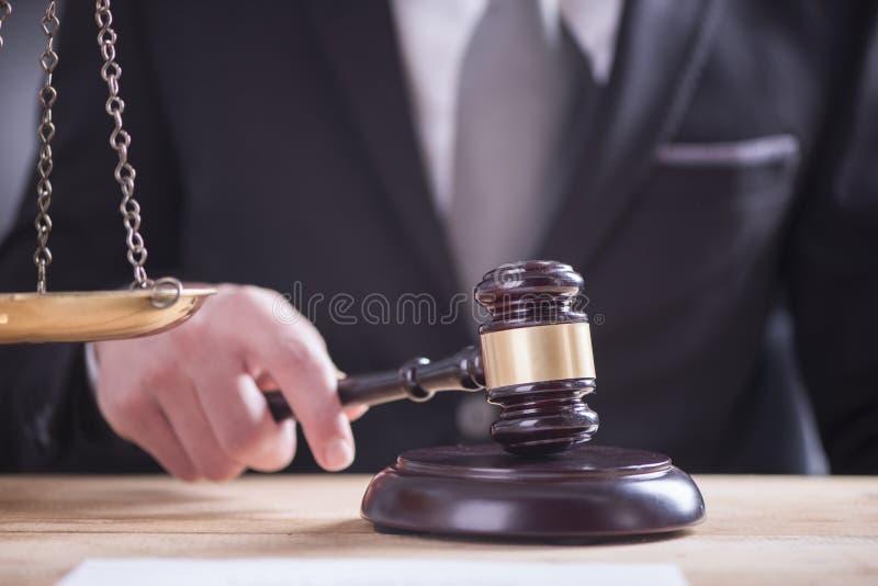Ciérrese para arriba del ` masculino s de la mano del abogado o del juez que pega el mazo encendido tan foto de archivo