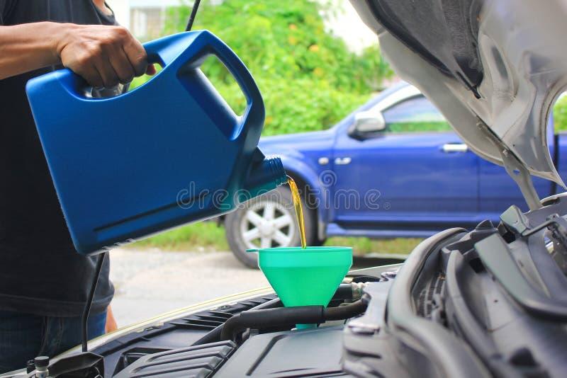 Ciérrese para arriba del mecánico que vierte el aceite fresco al motor de coche foto de archivo libre de regalías