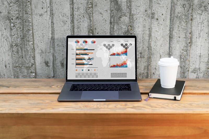 Ciérrese para arriba del ordenador portátil con los gráficos, las cartas, los horario en la pantalla y la taza de café en benchou imagenes de archivo