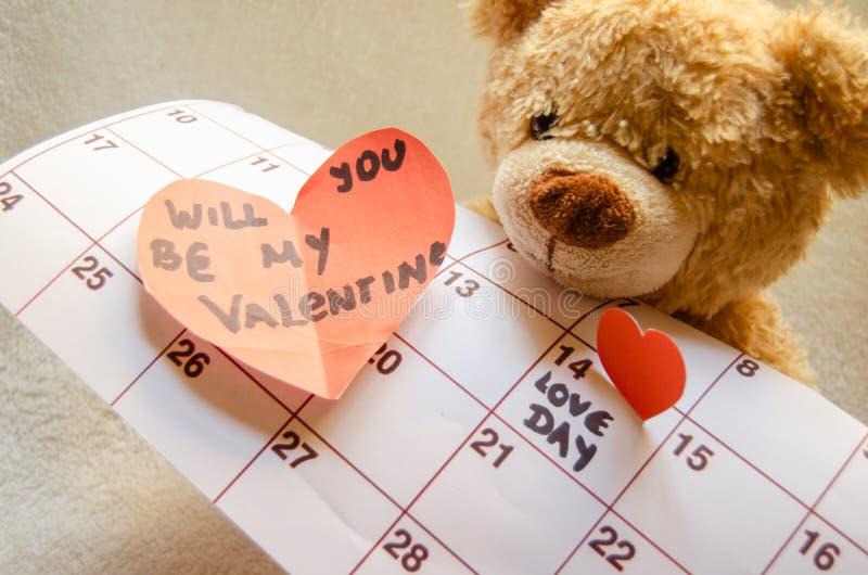 Ciérrese para arriba del oso de peluche que lleva a cabo el corazón rojo callendar y de papel amor día el 14 de febrero de marcad fotografía de archivo