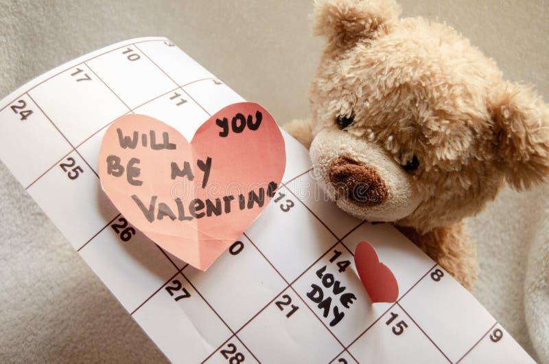 Ciérrese para arriba del oso de peluche que lleva a cabo el corazón rojo callendar y de papel amor día el 14 de febrero de marcad imagen de archivo