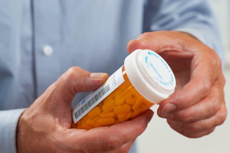 Ciérrese para arriba del paciente que vierte píldoras de RX fotografía de archivo libre de regalías