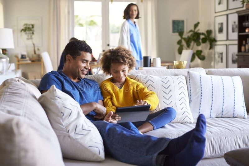 Ciérrese para arriba del padre joven que se sienta en el sofá en la sala de estar con su hija pre-adolescente que usa la tableta, imagen de archivo