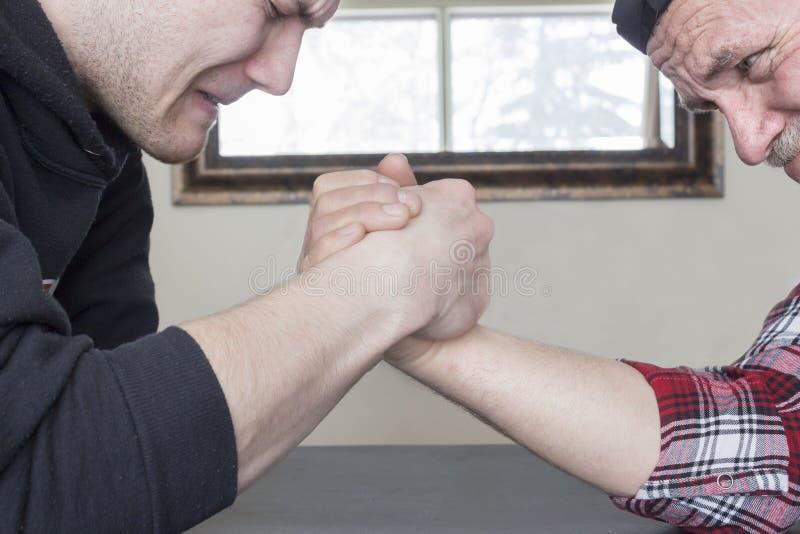 Ciérrese para arriba del padre y del hijo armwrestling fotografía de archivo