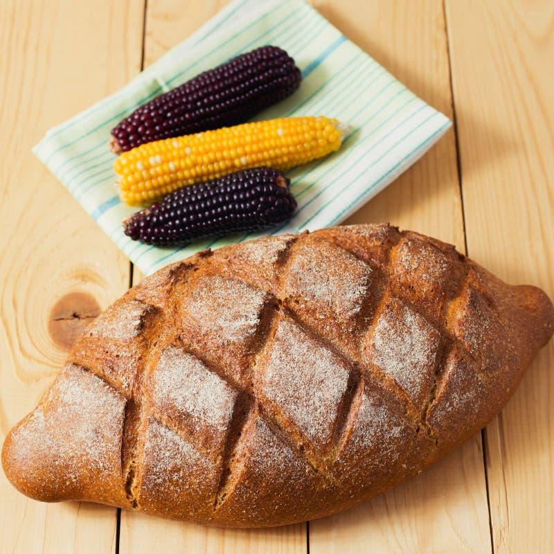 Ciérrese para arriba del pan fresco del trigo integral que pone en servilleta blanca verde en la tabla de madera con maíz negro y fotos de archivo libres de regalías