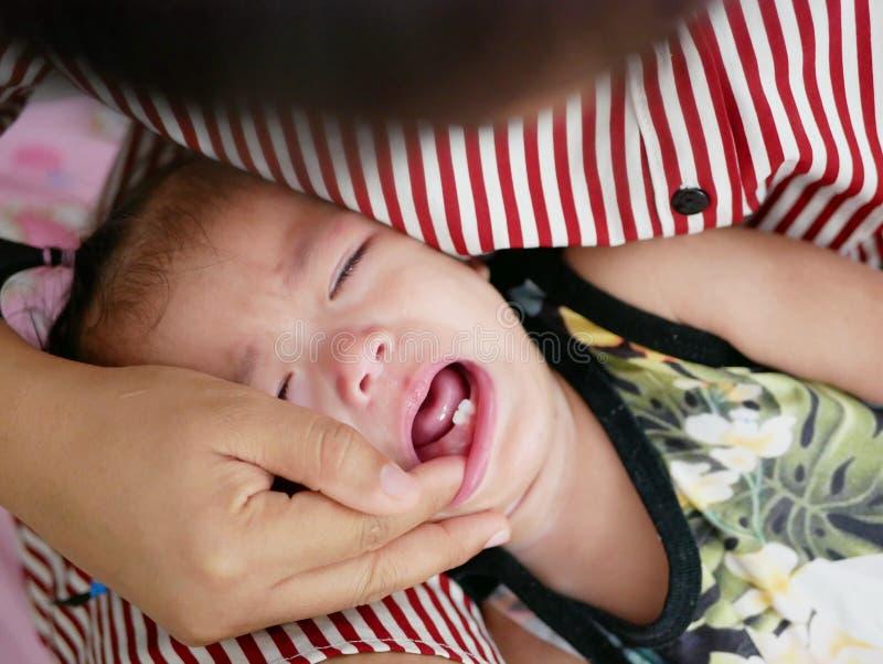 Ciérrese para arriba del pequeño bebé asiático, de un año, llorando como sus nuevos dientes que eliminan fotografía de archivo libre de regalías