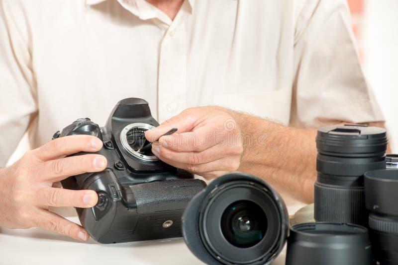Ciérrese para arriba del sensor de la limpieza de la mano del fotógrafo de su cámara imagen de archivo libre de regalías
