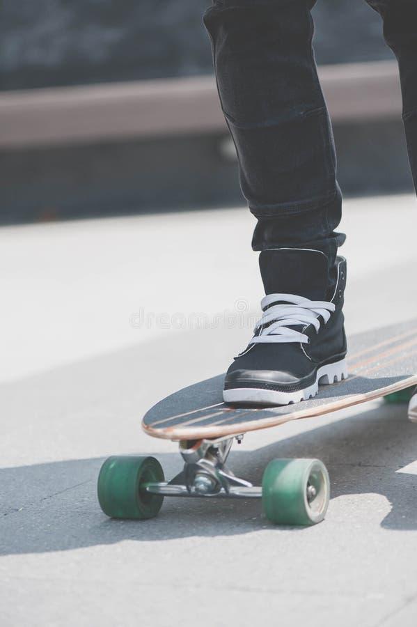Ciérrese para arriba del skater& x27; piernas de s en el montar a caballo del longboard en la calle adentro al aire libre fotografía de archivo libre de regalías